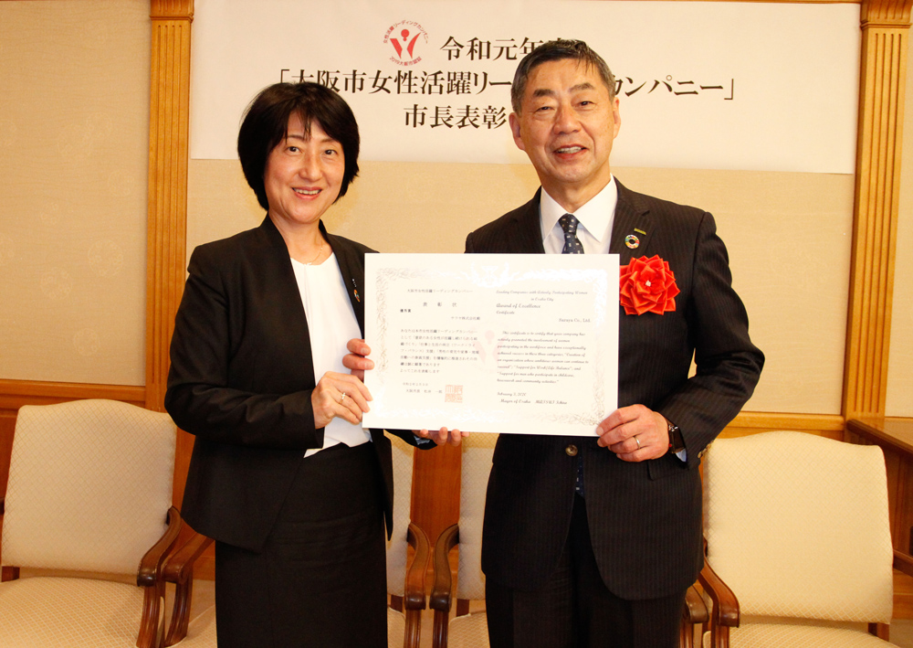 "HR Director Murai with President Saraya, holding the ""Leading Companies with Actively Participating Women in Osaka City"" Award"